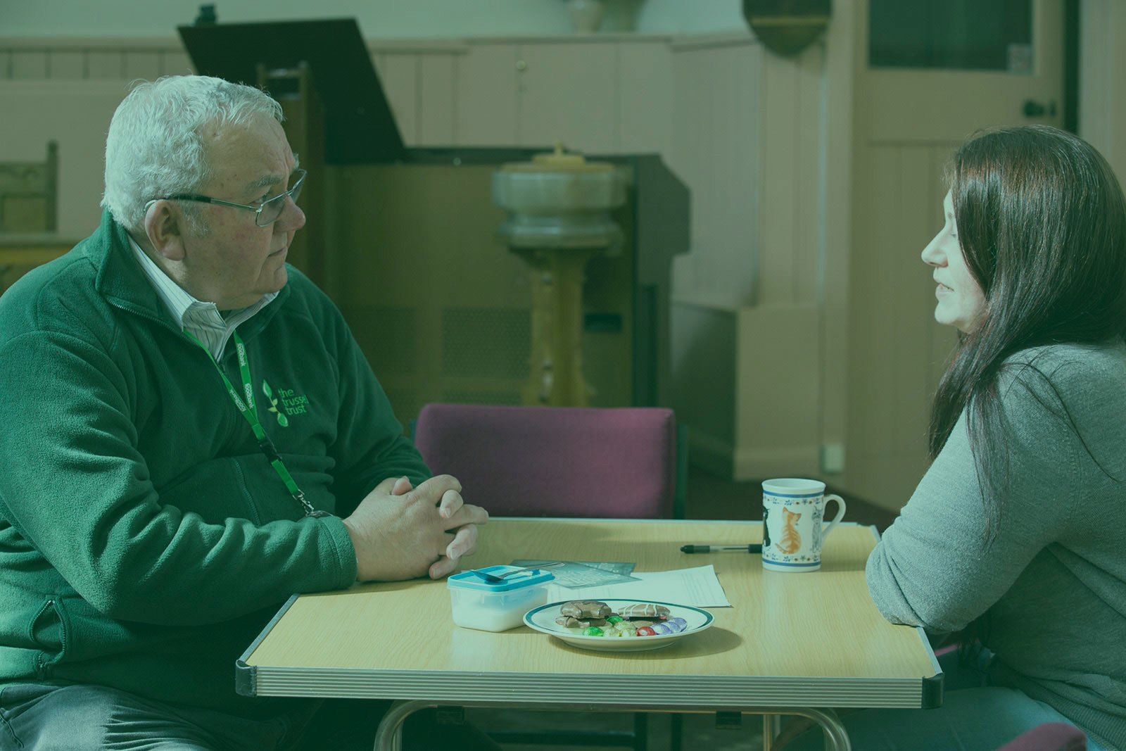 Trussell Trust volunteer sits with a foodbank visitor.